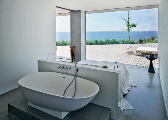 Dokonce i ložnice s vlastní vanou je otevřena do prostoru a nabízí výhledy do venkovní krajiny. (Zdroj: Schüco, foto: Kristine Mengel)