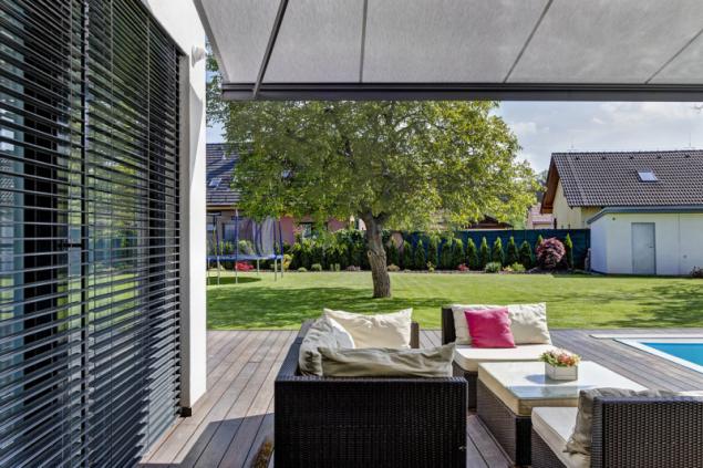 Pohled z terasy na zahradu, která je ohraničena plotem a řadou okrasných keřů, v pravé části se nachází malý zahradní domek