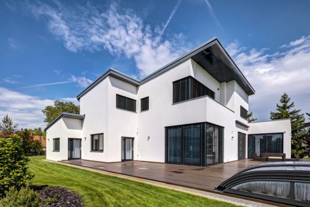 Dům je s venkovním prostorem maximálně propojen vizuálně i přímo posuvnými prosklenými stěnami. Rozsáhlá terasa navazuje na zastřešený bazén a odpočinkovou zahradu