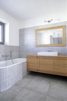 V patře se nově nachází prostorná koupelna s vanou i sprchou a s dostatkem úložných prostor, což si paní domu nemůže vynachválit
