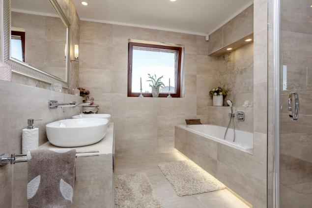 Koupelna je až po strop obložena velkoformátovými dlaždicemi, stěna sprchového koutu zároveň odděluje z jedné strany prostor pro vanu s osvětlenou nikou