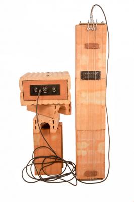 Keramosteel kytara z cihelného systému Porotherm. Steel kytara a sní spjatý styl hry byl vyvinut na Havajských ostrovech vprůběhu 19. st. Při hře je položen nástroj na kolenou hudebníka vhorizontální poloze. (Zdroj: Wienerberger)