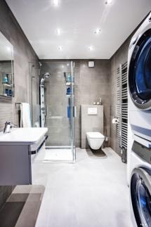 Koupelna v přízemí zahrnuje toaletu, sprchu a hlavně pračku se sušičkou, k níž vede z patra shoz prádla