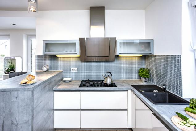 Elegantní kombinace bílé a šedé sluší i kuchyni zhotovené na míru. Paní domu má vše po ruce, pán domu zde našel místo i pro dvě malé vinotéky a sommeliérské potřeby
