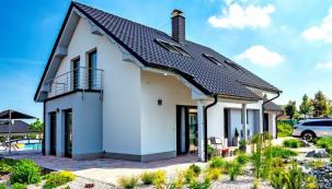 Klasické tvarosloví se šikmou střechou a kombinace bílé a modrošedé omítky s černou krytinou nezklamou v žádném kontextu, zde se však vyjímají přímo ukázkově