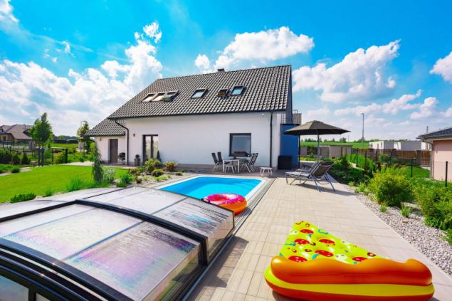 Pohled na dům z pečlivě udržované zahrady. Zastřešený bazén se slanou vodou rodina hojně využívá