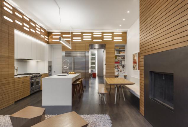 Zajímavým prvkem společenské části a kuchyně jsou vestavné skříně s podsvícenými dubovými stěnami.