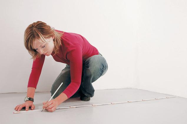 """1. Na podlaze vyměřte polohu příčky a """"brnkací šňůrou"""" nebo pomocí profilu vyznačte obrysovou čáru. Nezapomeňte na případné dveřní otvory. Potom s pomocí vodováhy a pravítka vyznačte obrysové linie příčky na stěnách a stropech. Pozor: vytyčuje se obvod konstrukce, proto je nutno zohlednit tloušťku opláštění"""