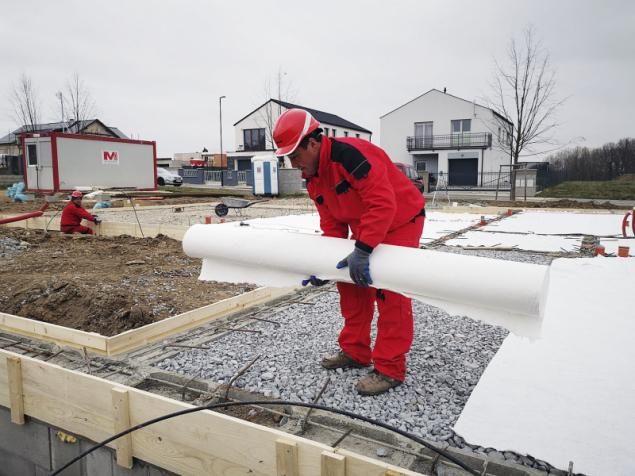 Pokládání geotextilie (odděluje a chrání materiály odlišné povahy) na vrstvu kameniva před betonáží základové desky
