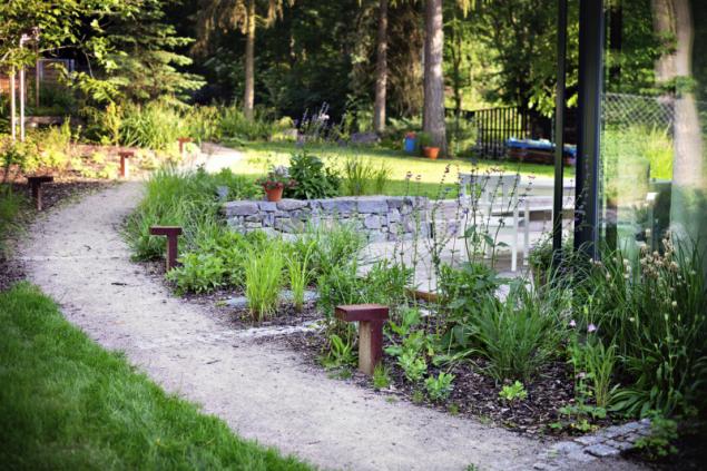 Neformální design zahrady skvěle doplňují mlatové cesty bez obruby, připomínající vyšlapanou lesní cestu. Decentní osvětlení z cortenu láká k procházce i v pozdních večerních hodinách