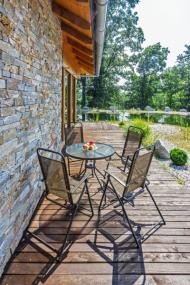 Fasáda domu je ze sukovatých prken sibiřského modřínu doplněných o pásy kvarcitového kamene. Dřevěná terasa propojuje obývací pokoj s hlavním vchodem a ložnicí