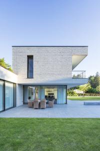 Na jedné straně domu byla vybudována zastřešená terasa. Je přístupná ze dvou obytných zón prostřednictvím prosklených posuvných systémů