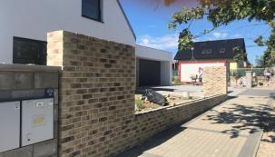 Ve venkovní části domu se provádí zděný plot z pálených cihel Terca. Základ byl proveden ze ztraceného bednění vylévaného betonem. Zmonolitněná konstrukce nese vyzdívaný plot a je podkladem pro nosnou část venkovní příjezdové brány vstupní branky (zdroj: Wienerberger)