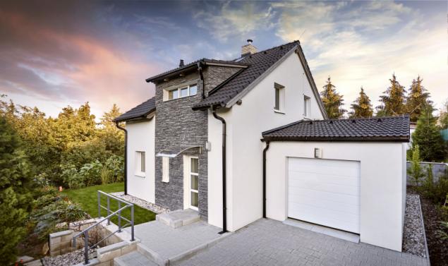 Obklad fasády imitující šedý štípaný kámen domu vyloženě sluší. Dodává mu osobitost a krásně ladí se střechou z betonových tašek