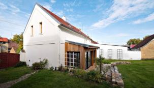 Přístavba z neupraveného modřínu je bezbariérově propojena s dřevěnou terasou a vymezena nízkými kamennými zídkami. Tabulková okna korespondují s historickým rázem domu