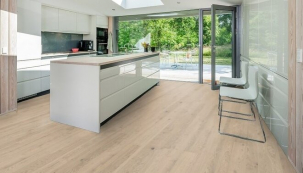 Protáhlý světlý interiér se s měnící se barvou dřevěné podlahy Kährs proměnil v opticky menší, teplejší prostor s výrazným kuchyňským ostrůvkem (zdroj: KPP)