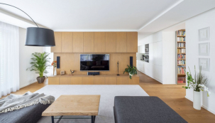 Velkorysý obývací prostor je rozdělen nábytkovou stěnou s televizí na obývací pokoj a kuchyň s jídelnou. Toto řešení je běžné i u řady rodinných domů