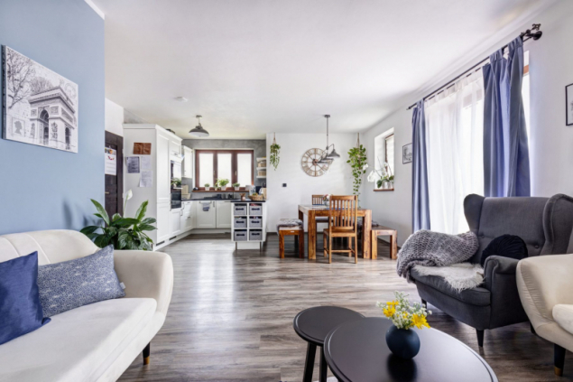 Pohled z odpočinkové zóny směrem do jídelní části a kuchyně ve tvaru písmene U. Jídelní stůl a židle jsou z masivního exotického dřeva s přírodní povrchovou úpravou
