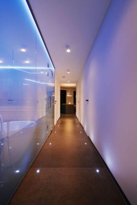 Dlouhá chodba je z jedné strany tvořena plnou stěnou s nenápadnými dveřmi se skrytou zárubní, z druhé prosklenou příčkou koupelny, která chodbu opticky rozšiřuje