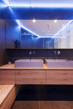 Do pohodlné koupelny se vešla vana, sprcha i dvě umyvadla Gravelli z betonu doplněná o úložné prostory, zrcadlo a ambientní osvětlení. Umyvadla dobře korespondují s betonovým obkladem