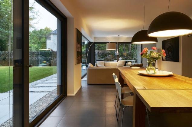 Protáhlý společný obývací prostor vyplňuje většinu dispozice přízemí a je plně orientován do klidové části zahrady