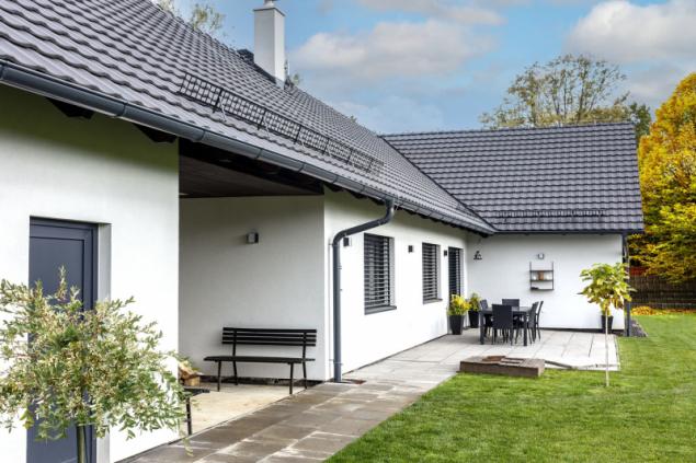 Předokenním venkovním žaluziím pomáhá při stínění přesah střechy. Prostor za domem je částečně vydlážděn, zbytek je zatravněn. Vnitřní roh písmena L je využit pro venkovní posezení