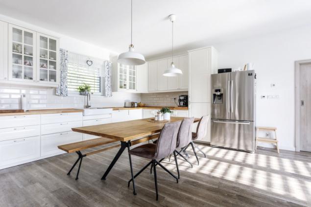 Kuchyně inspirovaná provensálským stylem s masivní dřevěnou deskou v přírodním odstínu. Stejný odstín najdete i na desce jídelního stolu a lavici minimalistické konstrukce