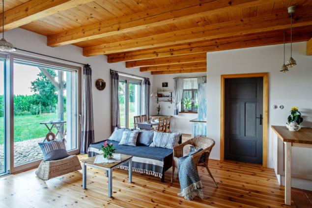 Společný obývací prostor. Strop a palubková podlaha jsou dílem Zorky a Stanislava a jsou sladěny s dveřními zárubněmi. Přírodní dřevo citlivě doplňují textilie v namodralých tónech