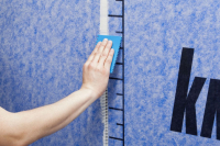 U okrajů pásů tkaniny je vyznačen pruh šířky 6 cm, který odpovídá šířce přesahu. Na tento pruh naneste MS polymerový tmel Knauf POWER-ELAST a vrstvu srovnejte ozubeným hladítkem s šíří zubu 2 mm