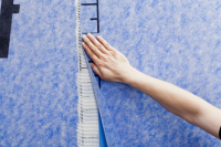 Na přesah přitiskněte další pás tkaniny a lehce stlačte. Pás přitiskněte a vyrovnejte plastovou stěrkou