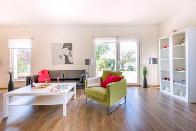 Obývací pokoj má francouzské okno na terasu a další dvě vertikální okna stíněná roletami. Interiéru udává tón podlaha s rustikálním dřevěným dekorem