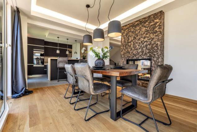 Dům je jako stvořený pro velkou rodinu nebo pro setkávání s početnou skupinou přátel. Všude je dostatek prostoru pro sezení a pohodlné stolování, ani v reprezentativní kuchyni nechybí barový pult